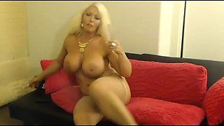 Busty blonde cougar in stockings fucks herself on the webcam