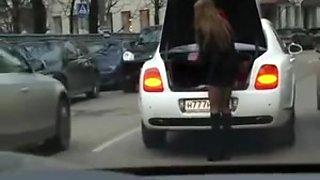 Girl changing shoes in miniskirt on street